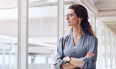 Buy stock photo Shot of a mature businesswoman looking thoughtfully out the window in an office