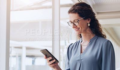 Buy stock photo Shot of a mature businesswoman using a cellphone in an office