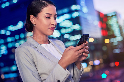 Buy stock photo Cropped shot of an attractive young businesswoman using her cellphone outdoors in the evening with the cityscape in the background