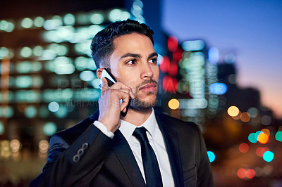 Buy stock photo Cropped shot of a handsome young businessman making phone calls in the city at night