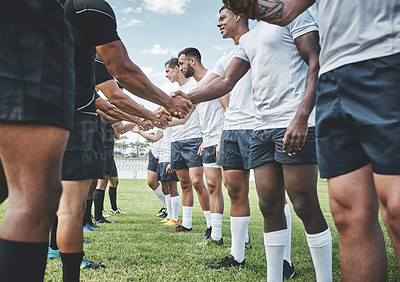 Buy stock photo Cropped shot of a group of young rugby players shaking each other's hands to congratulate in playing a good game outside on a filed