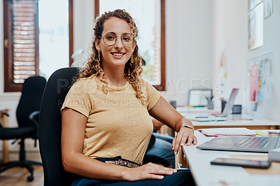 Buy stock photo Shot of a young businesswoman working at her desk in a modern office