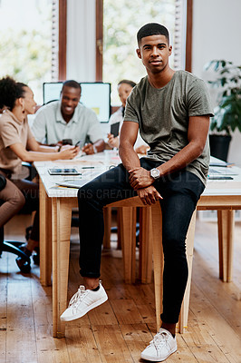 Buy stock photo Portrait of a confident young businessman with his team having a meeting in the background