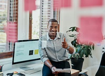 Buy stock photo Shot of a young businessman showing thumbs up in a modern office