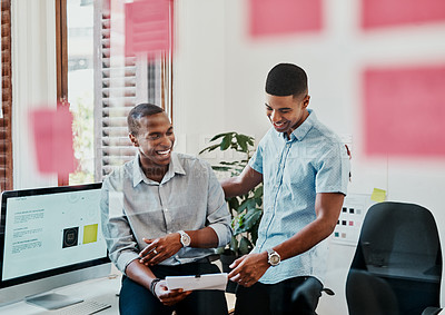 Buy stock photo Shot of two young businessmen going over paperwork in a modern office