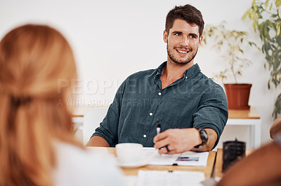 Buy stock photo Shot of a young businessman having a meeting with his colleagues in an office