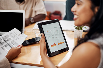 Buy stock photo Closeup shot of an unrecognisable businesswoman analysing graphs on a digital tablet with a colleague in an office