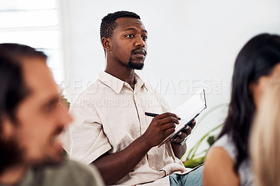Buy stock photo Shot of a young businessman writing notes during a conference