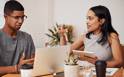Buy stock photo Shot of two businesspeople using a laptop and digital tablet while working together in an office