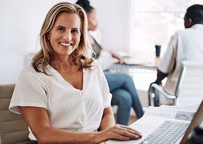 Buy stock photo Cropped portrait of an attractive young businesswoman sitting in her office with her coworkers and using her laptop