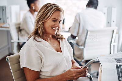 Buy stock photo Cropped portrait of an attractive young businesswoman sitting in her office with her coworkers and using her cellphone