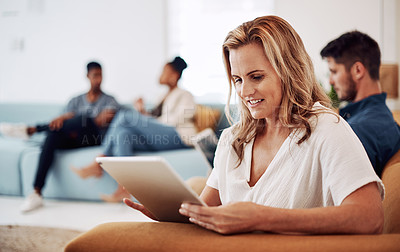 Buy stock photo Cropped shot of an attractive young businesswoman sitting and using a tablet while her colleagues work behind her