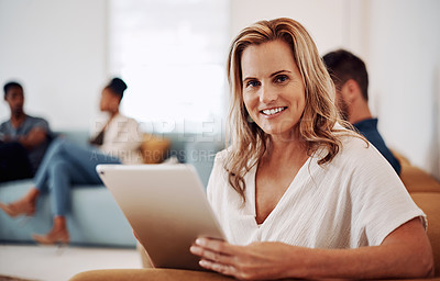 Buy stock photo Cropped portrait of an attractive young businesswoman sitting and using a tablet while her colleagues work behind her