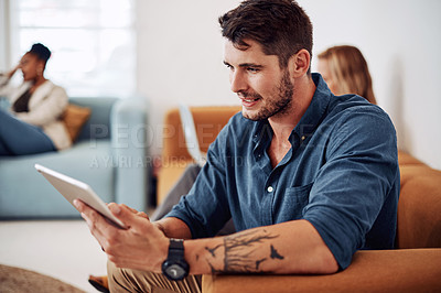 Buy stock photo Cropped shot of a handsome young businessman sitting and using a tablet while his colleague works beside him