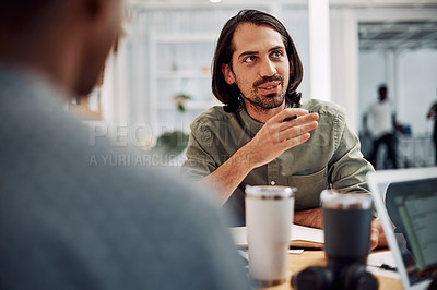 Buy stock photo Cropped shot of a handsome young businessman sitting with his male colleagues in the office