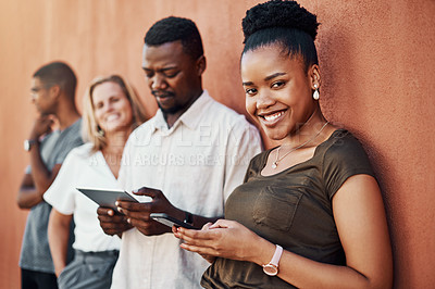 Buy stock photo Cropped portrait of an attractive young businesswoman standing with her colleagues outside and using her cellphone