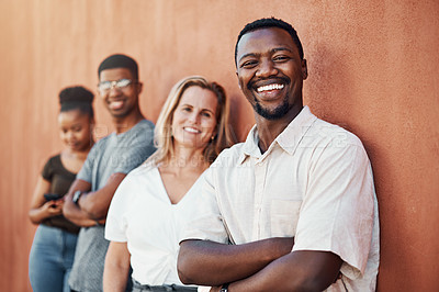 Buy stock photo Cropped portrait of a handsome young businessman standing with his colleagues against a wall outside