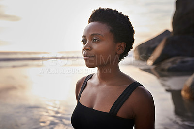 Buy stock photo Cropped shot of an attractive young woman relaxing and spending time alone on the beach at sunset