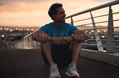 Buy stock photo Shot of a young man taking a break from working out in the city