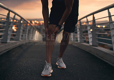 Buy stock photo Cropped shot of a man experiencing discomfort in his knee during a workout in the city at sunset