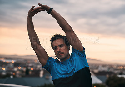 Buy stock photo Shot of a young man stretching while working out in the city