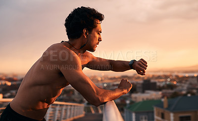 Buy stock photo Shot of a young man checking the time during a workout in the city
