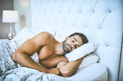 Buy stock photo Cropped shot of a handsome young man peacefully sleeping in his bed at home