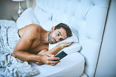 Buy stock photo Cropped shot of a handsome young man using his cellphone while lying in bed at home