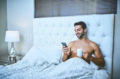 Buy stock photo Cropped shot of a handsome young man drinking coffee and using his cellphone while lying in bed at home