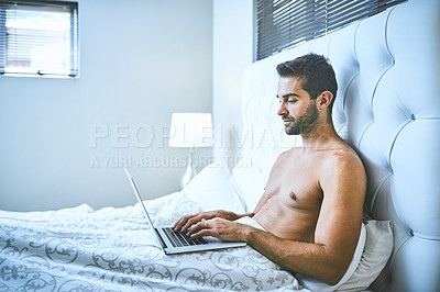 Buy stock photo Cropped shot of a handsome young man using his laptop while relaxing in bed at home
