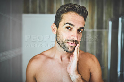 Buy stock photo Portrait of a handsome young man admiring and examining his face inside his bathroom at home