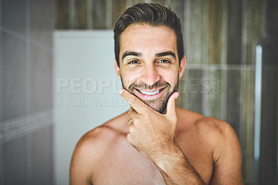 Buy stock photo Portrait of a handsome young man feeling cheerful and confident inside his bathroom at home