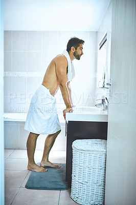 Buy stock photo Full length shot of a handsome young man looking at his face in the mirror inside his bathroom at home