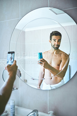 Buy stock photo Cropped shot of a handsome young man taking selfies with his cellphone inside his bathroom at home