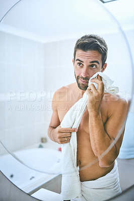 Buy stock photo Cropped shot of a handsome young man drying his face with a towel in the bathroom at home
