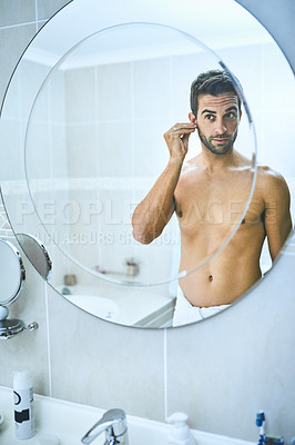 Buy stock photo Cropped shot of a handsome young man cleaning his ears with an earbud in the bathroom at home