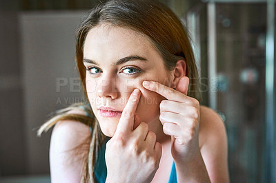 Buy stock photo Shot of a young woman squeezing pimples on her face in the bathroom at home
