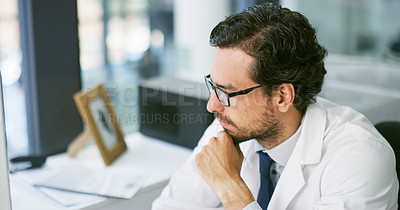 Buy stock photo Shot of a young doctor using a computer at his desk