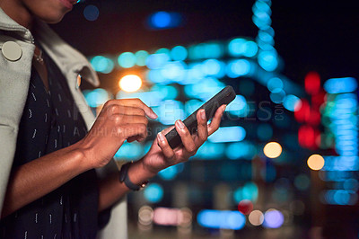 Buy stock photo Cropped shot of an unrecognizable businesswoman using her cellphone outdoors in the city at night