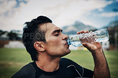 Buy stock photo Cropped shot of a handsome young rugby player drinking water while standing on the field during the day