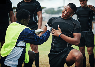 Buy stock photo Cropped shot of a young rugby player receiving first aid assistance on the field