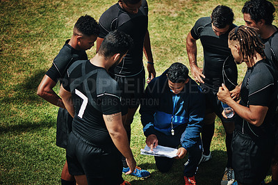 Buy stock photo High angle shot of a handsome young rugby coach addressing his team on the field during the day