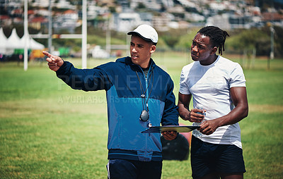 Buy stock photo Cropped shot of a handsome young rugby coach talking to one of his players on the field during the day