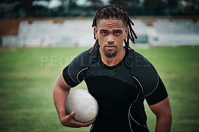 Buy stock photo Cropped portrait of a handsome young rugby player holding a rugby ball while standing on the field