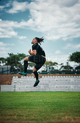Buy stock photo Full length shot of a handsome young rugby player jumping into the air while cheering on the field