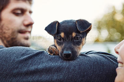Buy stock photo Shot of happy young man spending time with his adorable little puppy outside