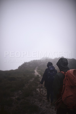 Buy stock photo Shot of two male friends out hiking in the mountains on a foggy day