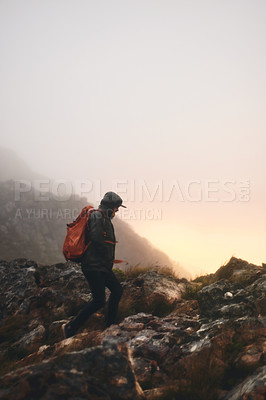 Buy stock photo Shot of a man wearing his backpack while out for a hike in the mountains