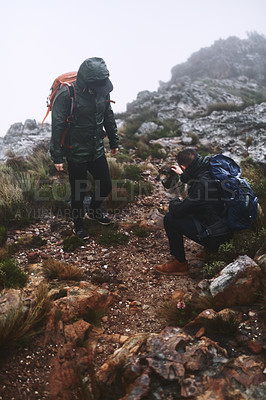 Buy stock photo Shot of two male friends out for a hike in the mountains with a dog