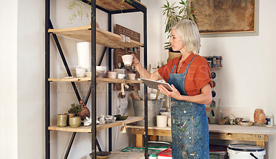 Buy stock photo Shot of a mature woman using a digital tablet while working in a pottery studio